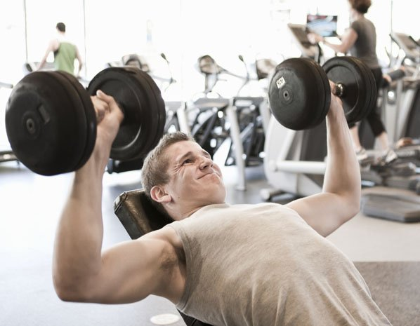 man lifting free weights in a fitness gym