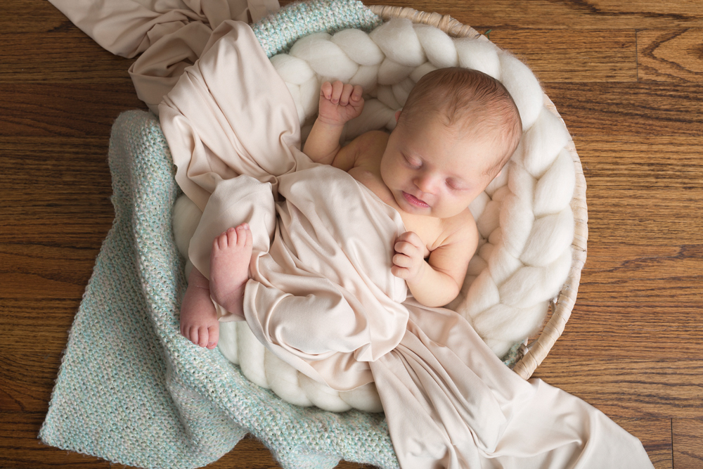 newborn girl in bowl with blanket