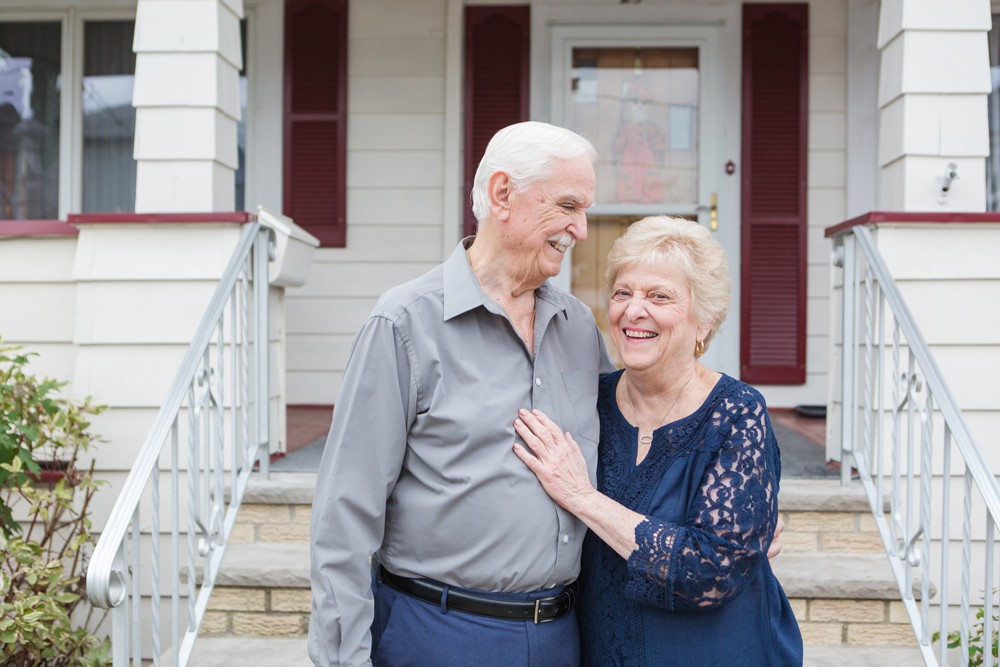 grandparents look at each other and laugh on front porch
