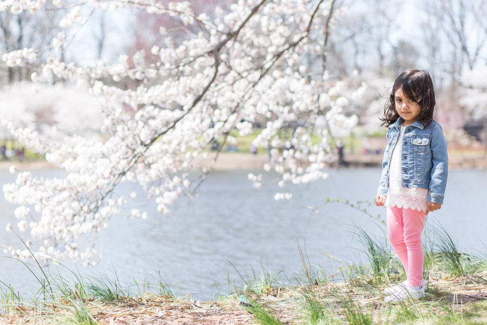 girl posing next to cherry blossom tree