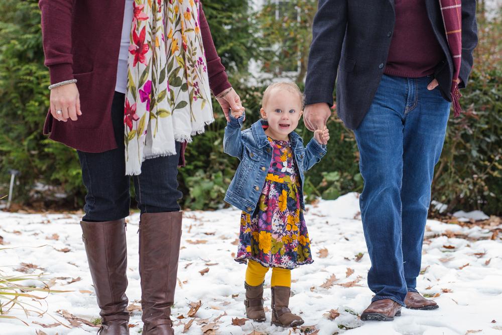 girl holding parents hands walking