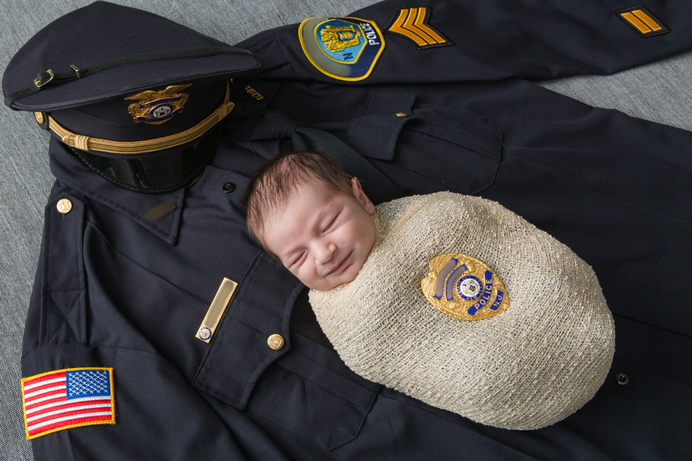 newborn baby on police uniform