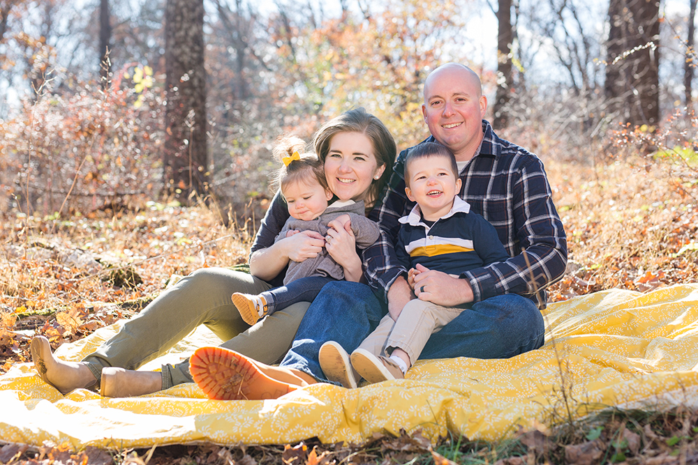 family of four posing in woods