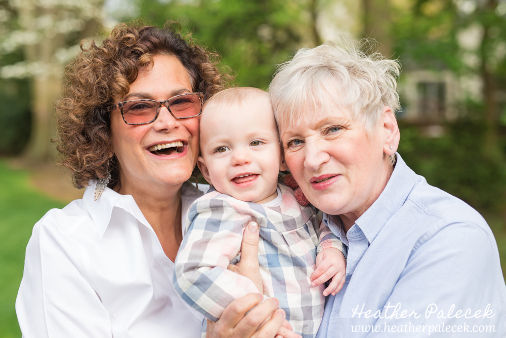 two grandmothers hold their granddaughter