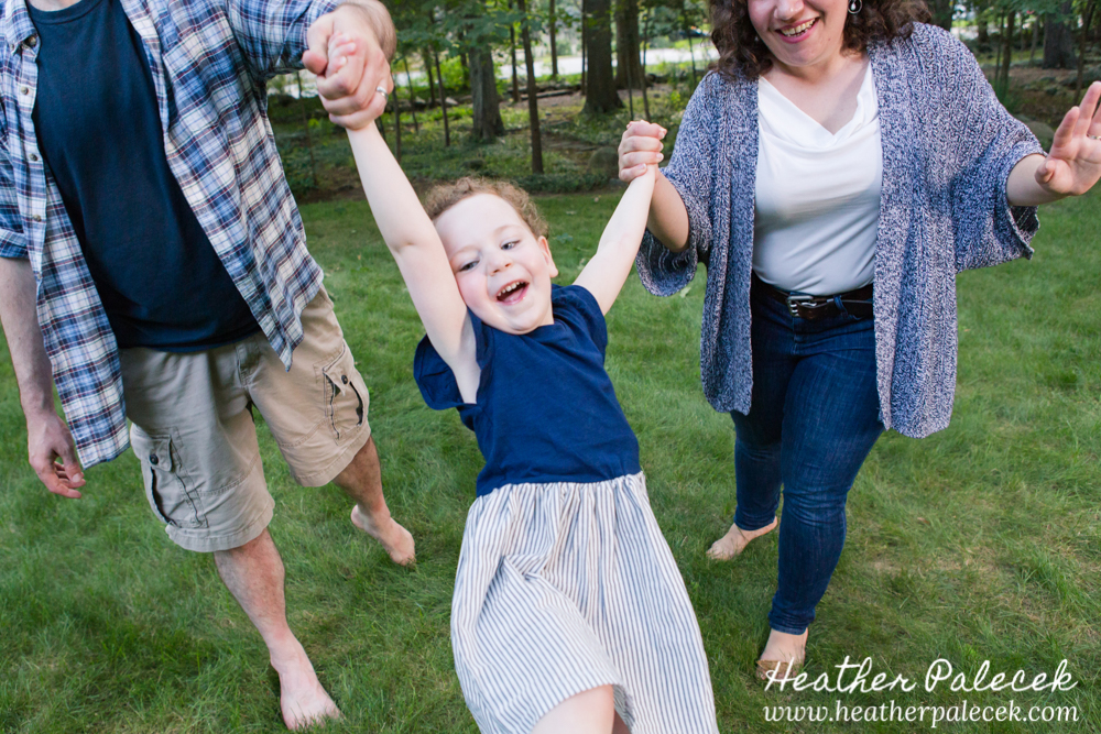 parents swing child in arir at family portrait bergen county nj