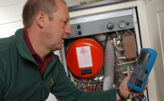 An OFTEC Registered technician checking for CO spillages