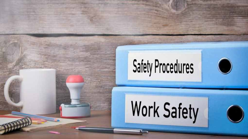 blue binders on workplace desk titled workplace safety