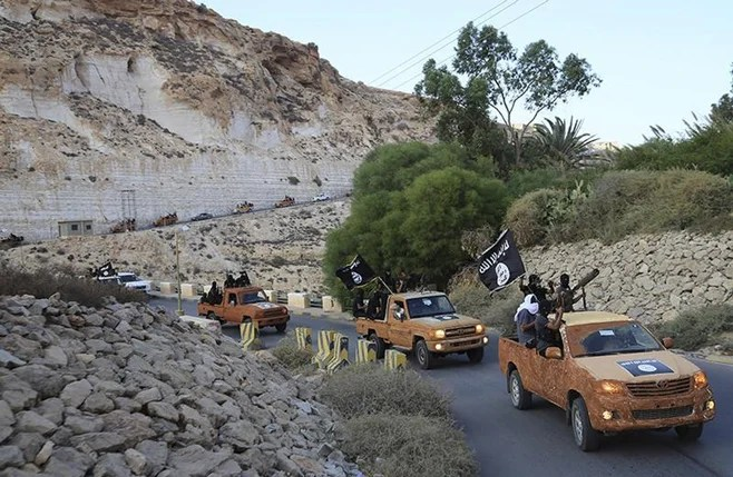 <p>An armed motorcade belonging to members of Derna's Islamic Youth Shura Council that pledged allegiance to ISIS, drive along a road in eastern Libya on October 3, 2014.</p>