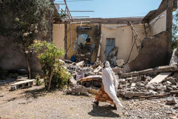 A woman walks past a house that was damaged by shelling when federal-aligned forces entered the town of Wukro, in Ethiopia's Tigray region, March 1, 2021.