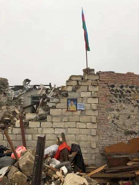 Uma foto emoldurada de um menino está pendurada em uma parede parcialmente destruída