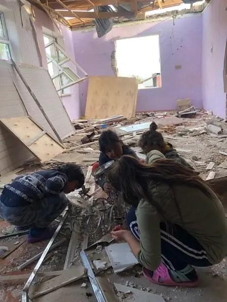 Crianças ajoelhadas dentro de um edifício danificado