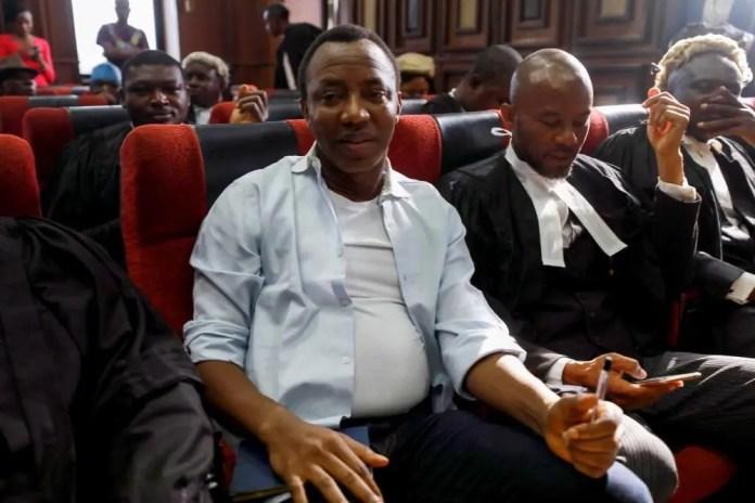 Um homem está sentado em um tribunal ao lado de advogados