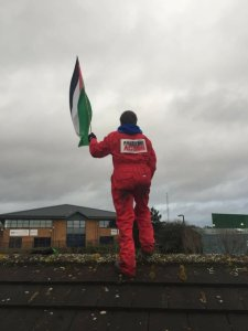 Bradley on Elbit roof with Palestinian flag