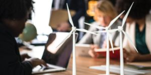 A multi-cultural group of people are seated at a table looking at laptops and books. In the foreground, models of wind turbines can be seen