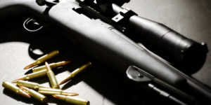 This photo shows part of a rife can be seen in dramatic lighting. Individual bullets are placed near the trigger.
