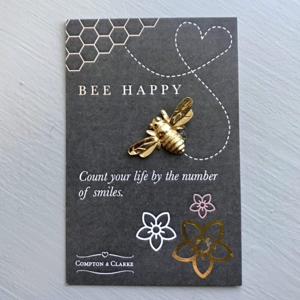 gold bee on a grey card