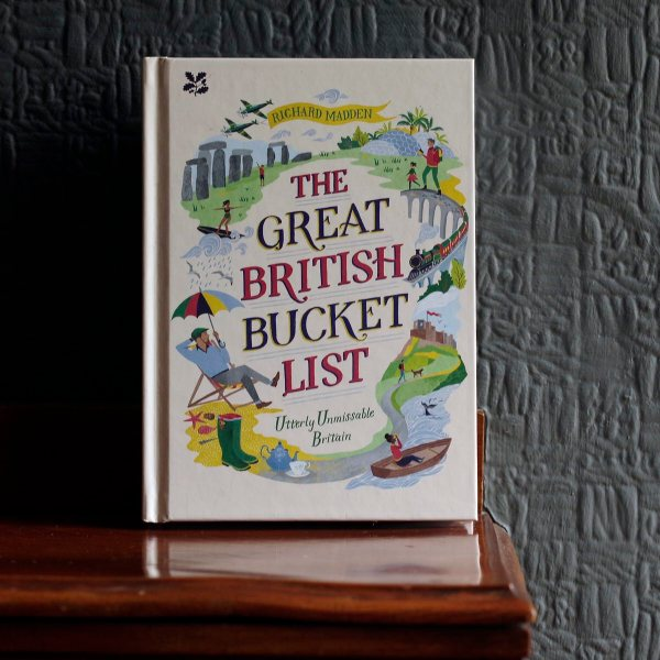 The Great British Bucket List is a colourful book standing on a wooden mantelpiece