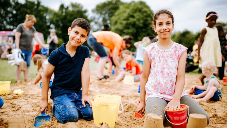 Two children play in the sand at a beach-themed activity day in a Hull Park.