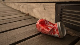 An empty drinks can thrown on the ground.