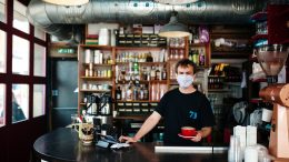 A person serves coffee indoors. They wear a facemask