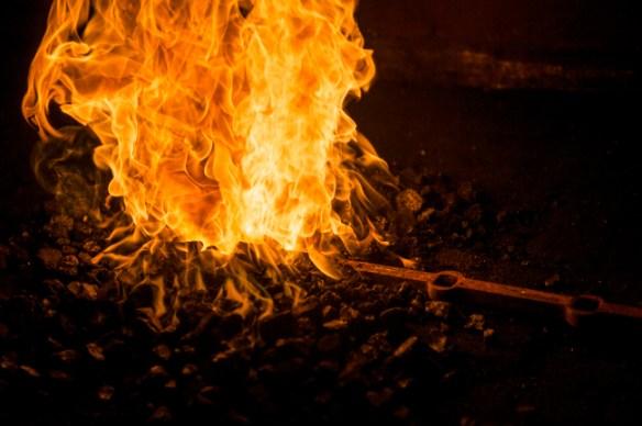 La barre d'acier est mise au feu pour être travaillée.