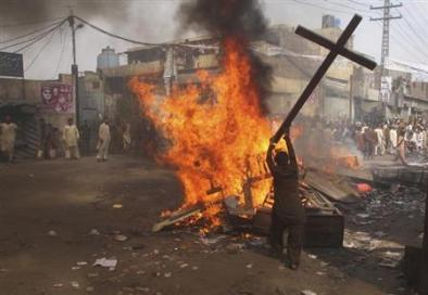 A demonstrator burns a cross during a protest in the Badami Bagh area of Lahore March 9, 2013. REUTERS/Adrees Hassain