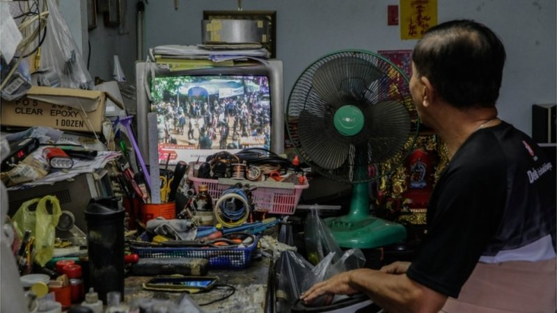 A man is pictured watching the news of the boys' rescue on a television in nearby Chiang Rai