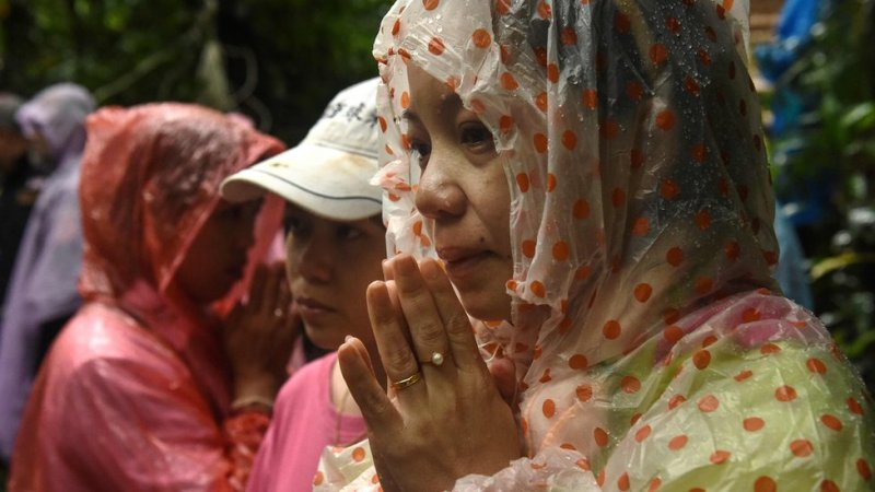 A woman is pictured praying in waterproof hood outside of site