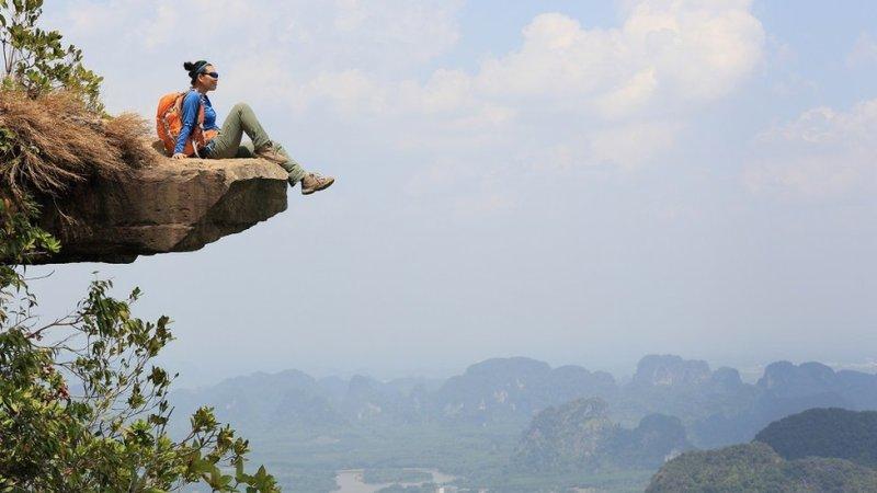 ایک خاتون پہاڑ سے وادی کا نظارہ کرتے ہوئے