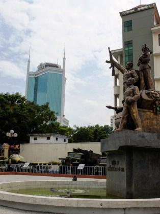 Небостъргач с минарета на покрива, камиони и самолети, останали от войната и паметник на загиналите