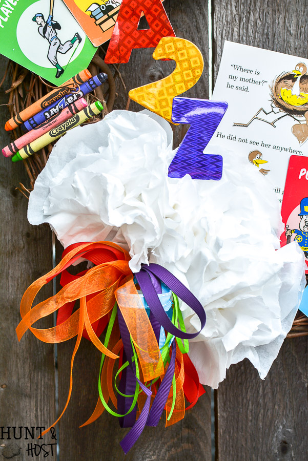 Need a fun teacher appreciation gift idea? This DIY teacher wreath is sure to be a hit, made from all the school supply leftovers, game pieces and miscellaneous office supplies show your favorite teacher some love with cute classroom decor!