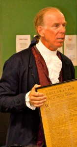 ray brown standing dressed as colonial American holding framed copy of U.S. Constitution