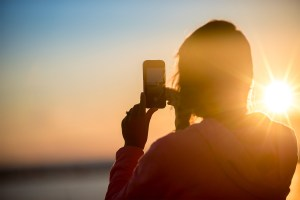 woman holding smartphone to take photo at sunset