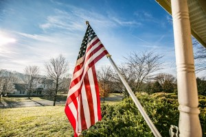 american flag flying off porch