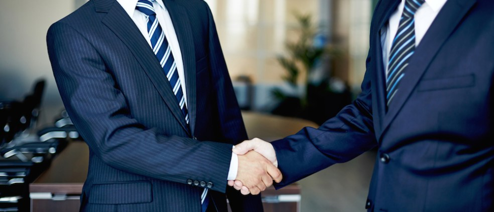 Two businessmen in navy blue suits shaking hands