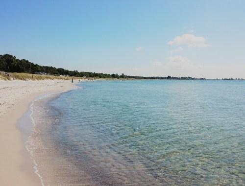 Sandstrand med blått vatten.