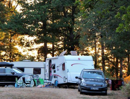 husvagnar och bilar på en naturcamping.