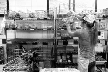 woman from behind sorting bagels
