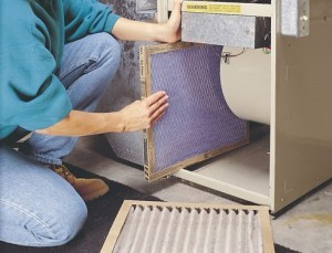 person changing air filter on hvac system