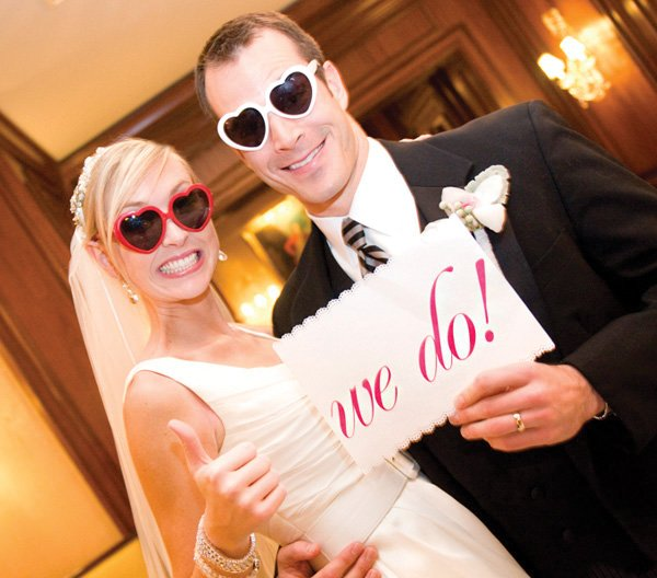 bride and groom after the ceremony holding a 'we do' sign