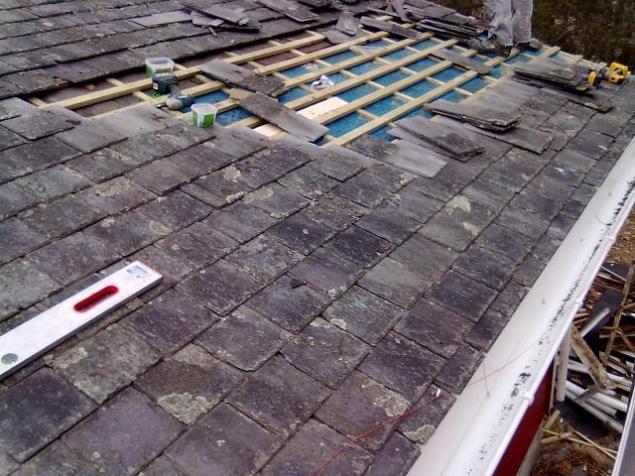 Legger tilbake skifersten på taket