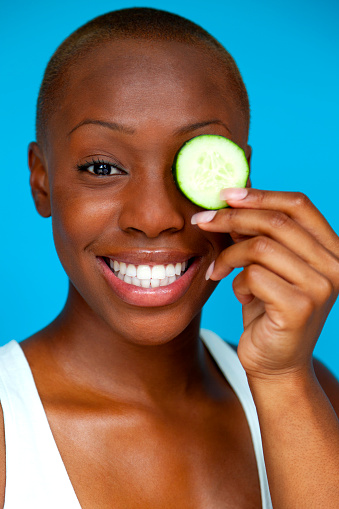 Smiling Woman Holding Cucumber Slice over Eye