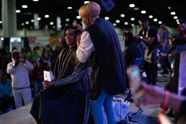 A hairstylist cuts hair on stage at the Bronner Bros. International Beauty Show.