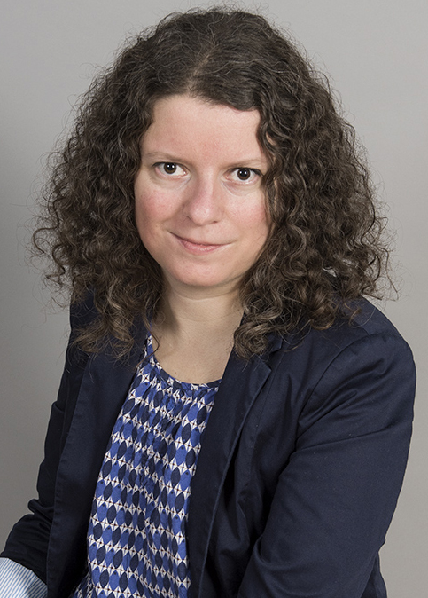 Maria Niemi med sitt långa, lockiga, mörka hår, en marinblå kavaj och en blåmönstrad blus
