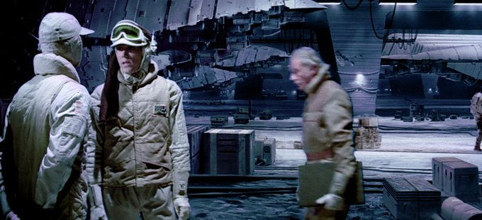 In The Empire Strikes Back. Ralph McQuarrie can be seen walking with his sketchbook in front of his own matte painting.