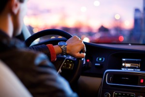 man wearing watch steering car