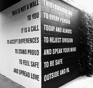 Two sides of a corner wall with words about accepting differences and welcoming every person is painted in black and white.