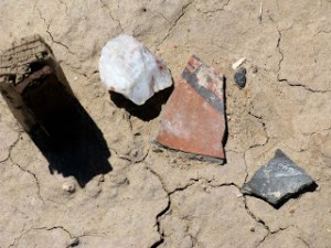 Pottery shards and a hide-scraper at Piedras Marcadas pueblo (click on image to source).