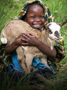 To the child in the picture, this goat feels the same as a dog or cat pet in America, but also supplies much-needed milk on a daily basis. Click on this picture to see how to give a goat for Christmas.