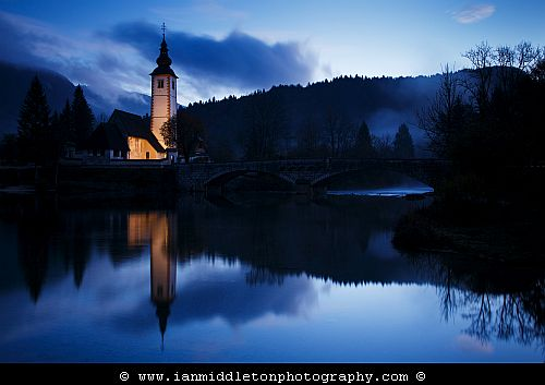 Dawn light over Lake Bohinj and the church of Saint John (Sveti Janez), Triglav National Park, Slovenia